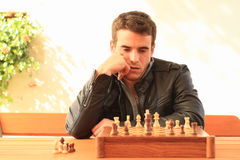 Young man playing chess royalty free stock photography