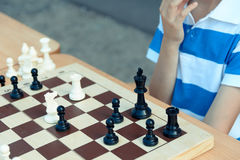 Young man playing chess. Photo of a young man coming up over the next chess move stock images