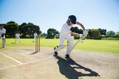 Young man playing cricket at field against clear sky. Young men playing cricket at field against clear sky on sunny day stock images