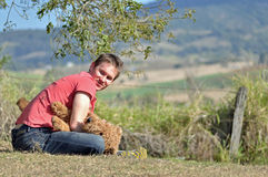 Young man playing with dog in countryside Stock Image