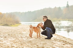 Young man playing with dog near the river Stock Images
