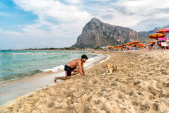 Young man playing with a dog on the San Vito Lo Capo beach on a cloudy day. Stock Photography