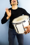 Young man playing drum. Happy young multiracial man playing a drum Stock Photography