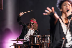 Young man playing drums set with singer on stage Stock Photos