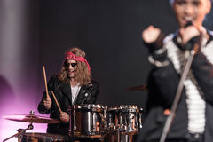 Young man playing drums set with singer on stage Stock Image