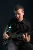 Young man playing electric bass guitar. On dark background Royalty Free Stock Images