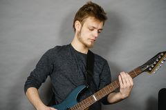 Young man playing electric guitar Stock Images