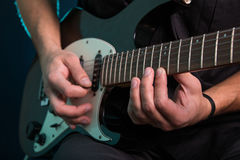 Young man playing electric guitar. On dark background Royalty Free Stock Photography