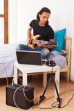 Young man playing electric guitar at home Stock Image