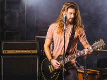 Young man playing electric guitar on stage. Photo of a young man with long hair and beard playing electric guitar on stage Royalty Free Stock Photos