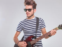 Young man playing electric guitar in studio Royalty Free Stock Photography