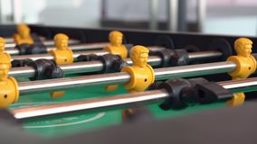 Young man playing enjoy foosball wooden table soccer game. Close-up yellow players, young man playing enjoy foosball wooden table soccer game stock video footage