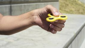 Young man playing with a fidget spinning stock footage