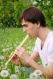 Young man playing on flute side view Stock Image
