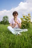 Young man playing on flute at summer time Royalty Free Stock Photo