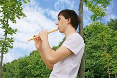 Young man playing on flute at summer time Royalty Free Stock Image