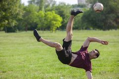 Young man playing football in park keeping ball in the air stock photo