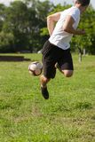 Young man playing football in park keeping ball in the air stock image
