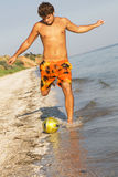 Young man playing football on a sea shore Royalty Free Stock Images