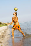 Young man playing football on a sea shore. Handsome young man playing football on a sea shore Royalty Free Stock Photography