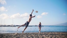 A young man playing frisbee on the beach with his female friend. Catching the disc and falling on the sand. Mid shot stock footage