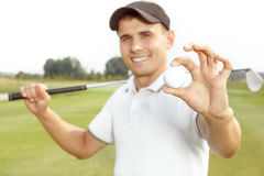 Young man playing a game of golf. Handsome young man playing a game of golf Royalty Free Stock Image