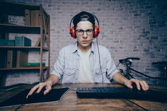 Young man playing game at home and streaming playthrough or walk. Through video. Attractive guy in cab and earphones looking at the camera. He seems to be Stock Photos
