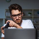 Young man playing games long hours late in the office stock images