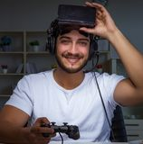 Young man playing games long hours late in the office royalty free stock photos