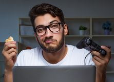 Young man playing games long hours late in the office royalty free stock images
