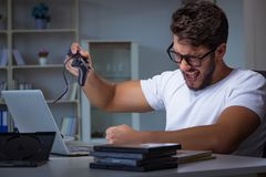 The young man playing games long hours late in the office. Young man playing games long hours late in the office Royalty Free Stock Photos