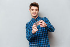 Young man playing games on smartphone. Young concentrated man wearing casual playing games on smartphone royalty free stock photo