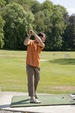 Young man playing golf at the driving range Royalty Free Stock Photo