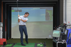Young man playing golf and interacting with video-game Royalty Free Stock Image