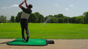 A young man playing golf near the golf field stock footage