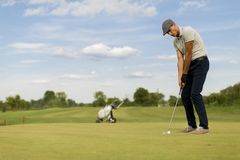 Young man playing golf. At sunny day Stock Image