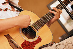 Young man playing guitar. Young man playing acoustic guitar showing hand position and strumming Royalty Free Stock Photo