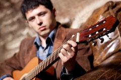 Young man playing on guitar. Sitting in a chair. Focus on hand Stock Photos