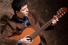 Young man playing on guitar. Camera angle view Stock Photos