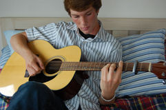 Young Man Playing Guitar. A young man playing guitar on his bed Stock Photography