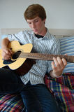 Young Man Playing Guitar. A young man playing guitar on his bed Stock Images