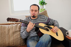 Young man playing the guitar. Young man playing acoustic guitar at home Stock Photos