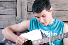 Young man playing the guitar. Image showing a guy playing his acoustic guitar stock photography