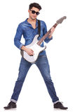 Young man playing guitar. Young casual man playing a guitar on a white background Royalty Free Stock Photos