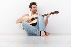 Young man playing guitar. Handsome young man playing guitar, sitting on floor Stock Images