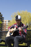 Young man playing guitar. On beautiful sunny day Royalty Free Stock Image
