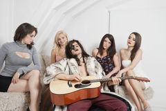 Young man playing guitar amid female friends Stock Image