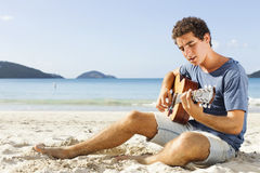 Young man playing guitar on the beach Royalty Free Stock Photography