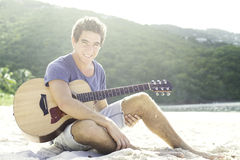 Young man playing guitar on the beach Stock Photos
