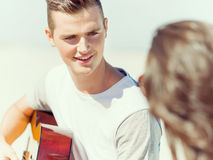 Young man playing guitar on beach Royalty Free Stock Photo